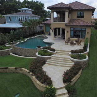Large mediterranean beige two-story stucco house exterior idea in Orlando with a hip roof and a tile roof