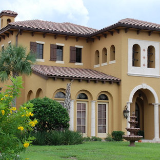 Inspiration for a huge mediterranean yellow two-story stucco gable roof remodel in Orlando