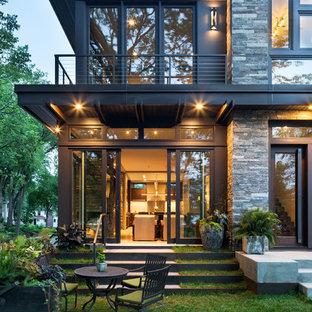Esempio della facciata di una casa piccola grigia moderna a due piani con rivestimenti misti e tetto piano