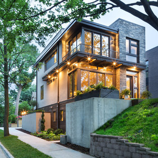 На фото: маленький, двухэтажный, серый дом в стиле модернизм с комбинированной облицовкой и плоской крышей