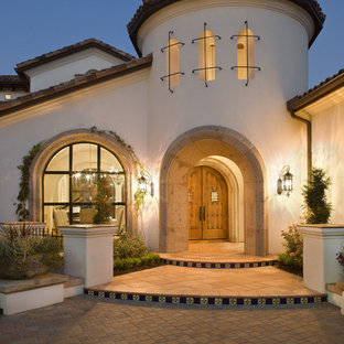 Photo of a mediterranean two-storey exterior in Austin with a tile roof.