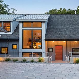 Diseño de fachada gris, contemporánea, grande, de tres plantas, con revestimiento de metal y tejado a dos aguas