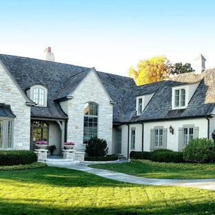 Foto della facciata di una casa beige classica a due piani con rivestimento in pietra