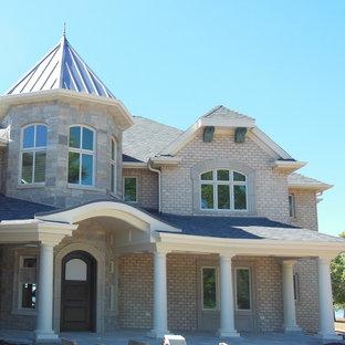 Ejemplo de fachada de casa beige, bohemia, grande, de tres plantas, con revestimiento de ladrillo, tejado a la holandesa y tejado de teja de madera