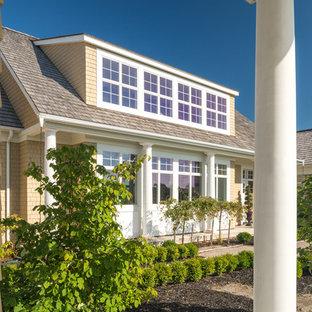 Modelo de fachada beige, costera, de tamaño medio, de dos plantas, con revestimientos combinados