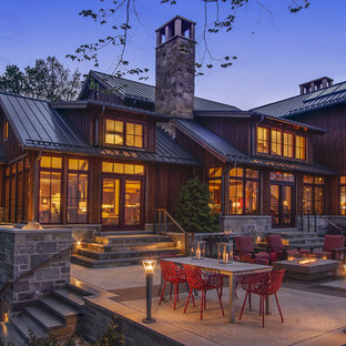 Rustic stone exterior home idea in Milwaukee with a metal roof