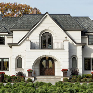 Example of a large classic white two-story stucco house exterior design in Minneapolis with a shingle roof and a hip roof