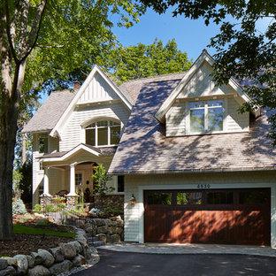 Diseño de fachada de casa beige, tradicional, de dos plantas, con revestimientos combinados, tejado a dos aguas y tejado de teja de madera