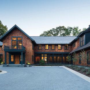 Immagine della facciata di una casa unifamiliare ampia marrone american style a due piani con rivestimento in legno, tetto a capanna e copertura mista