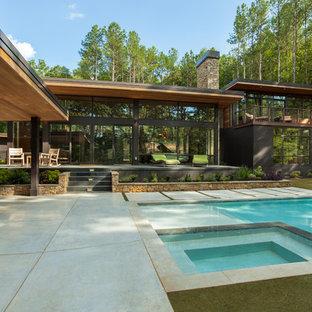 Imagen de fachada negra, minimalista, de tamaño medio, de dos plantas, con revestimientos combinados y tejado plano