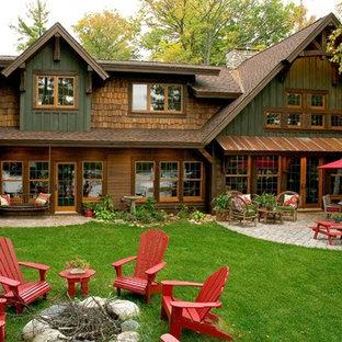 Foto della facciata di una casa verde rustica a due piani con rivestimento in legno