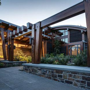 Immagine della facciata di una casa unifamiliare grande multicolore contemporanea a un piano con rivestimento in legno e copertura in metallo o lamiera