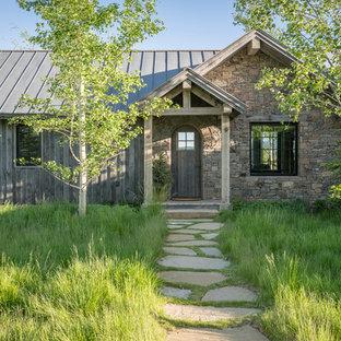 Ispirazione per la facciata di una casa unifamiliare marrone rustica a un piano con rivestimenti misti, tetto a capanna e copertura in metallo o lamiera