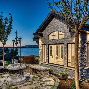 Imagen de fachada beige, clásica, extra grande, de dos plantas, con revestimiento de piedra, tejado a dos aguas y tejado de teja de madera