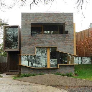 メルボルンのコンテンポラリースタイルのおしゃれな二階建ての家 (レンガサイディング、陸屋根) の写真