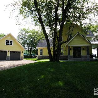 Imagen de fachada amarilla, campestre, grande, de dos plantas, con revestimientos combinados