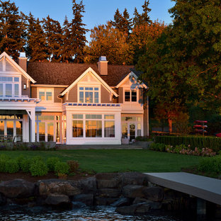 Inspiration for a large traditional two-storey grey house exterior in Seattle with wood siding, a clipped gable roof and a shingle roof.