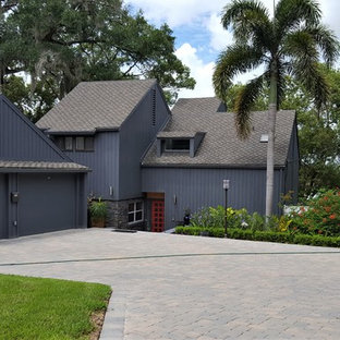 Inspiration for a mid-sized contemporary black three-story wood exterior home remodel in Orlando with a shingle roof