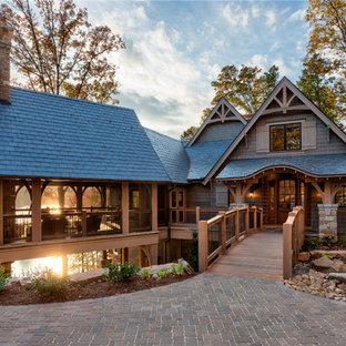 Immagine della facciata di una casa grande marrone classica a due piani con rivestimento in legno e tetto a capanna