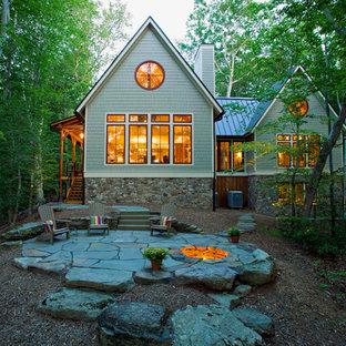 Idee per la facciata di una casa unifamiliare grande grigia rustica a un piano con rivestimento in legno, tetto a capanna e copertura in metallo o lamiera