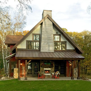 Inspiration for a rustic two-story metal exterior home remodel in Minneapolis with a mixed material roof
