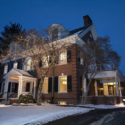 Example of a mid-sized classic red two-story brick exterior home design in Other
