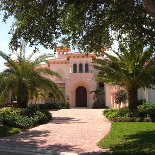 Example of a huge tuscan pink two-story stucco exterior home design in Miami with a hip roof