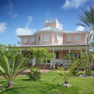 マイアミのトロピカルスタイルのおしゃれな二階建ての家 (ピンクの外壁) の写真
