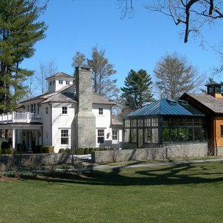 Foto de fachada blanca, ecléctica, grande, de tres plantas, con revestimiento de vinilo y tejado a cuatro aguas
