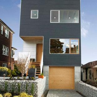Imagen de fachada negra, contemporánea, de tres plantas, con tejado plano
