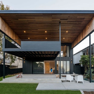 Design ideas for a contemporary two-storey black house exterior in Brisbane with concrete fiberboard siding and a flat roof.