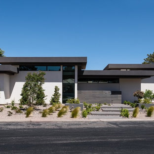 Example of a large minimalist white one-story stucco flat roof design in Las Vegas