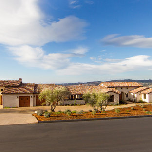 Example of a mid-sized tuscan beige one-story stucco gable roof design in San Luis Obispo