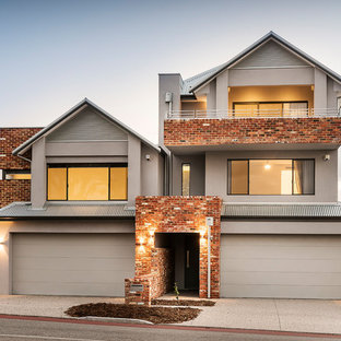 Design ideas for a transitional stucco beige duplex exterior in Perth with three or more storeys and a gable roof.