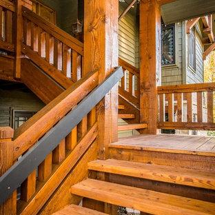 Diseño de fachada de casa verde, rústica, grande, de dos plantas, con revestimiento de madera, tejado a dos aguas y tejado de teja de madera
