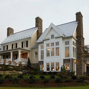 Diseño de fachada de casa beige, clásica, grande, de dos plantas, con revestimientos combinados, tejado a dos aguas y tejado de metal