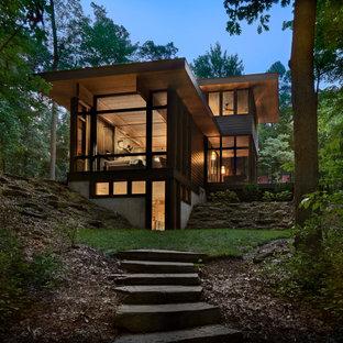 На фото: трехэтажный, черный частный загородный дом среднего размера в стиле рустика с облицовкой из ЦСП, плоской крышей и зеленой крышей