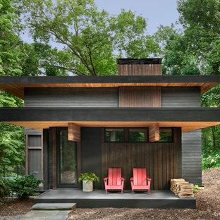 Idéer för att renovera ett mellanstort rustikt svart hus, med tre eller fler plan, fiberplattor i betong, platt tak och levande tak