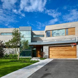 На фото: большие, двухэтажные фасады домов серого цвета в современном стиле с облицовкой из камня и плоской крышей