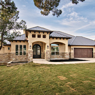 Example of a tuscan stone exterior home design in Austin with a metal roof