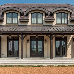 На фото: большой, двухэтажный, бежевый частный загородный дом в классическом стиле с крышей из смешанных материалов с