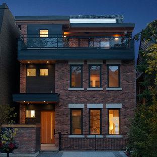Foto de fachada ecléctica, de tamaño medio, de tres plantas, con revestimiento de ladrillo y tejado plano