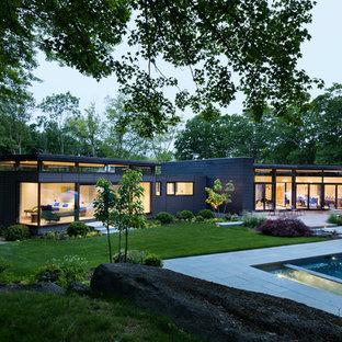 Foto på ett funkis svart hus, med allt i ett plan, platt tak och blandad fasad