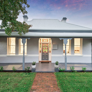 Design ideas for a transitional one-storey white exterior in Perth with a hip roof and a metal roof.