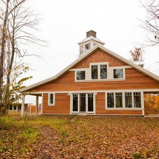 Idee per la facciata di una casa unifamiliare marrone country a due piani con rivestimento in legno, tetto a capanna e copertura in metallo o lamiera