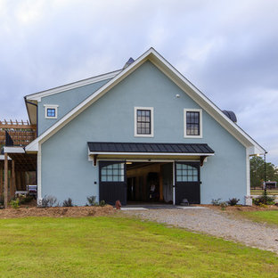 Example of a large farmhouse green two-story stucco gable roof design in Raleigh