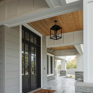 Ejemplo de fachada de casa blanca, de estilo de casa de campo, grande, de dos plantas, con revestimientos combinados, tejado a dos aguas y tejado de metal
