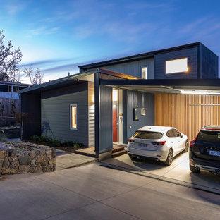 Modern inredning av ett litet grått hus, med två våningar, platt tak och tak i metall