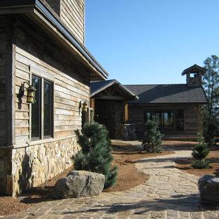 Modelo de fachada marrón, vintage, extra grande, de dos plantas, con revestimientos combinados y tejado a dos aguas