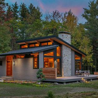Cette photo montre une petit façade de maison grise rétro de plain-pied avec un revêtement en panneau de béton fibré, un toit à deux pans et un toit en shingle.